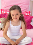 Little girl sitting on bed Stock Photography