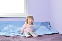 Little girl sitting on bed. Stock Photo