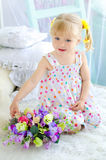 Little girl sitting on bed with bouquet of flowers Royalty Free Stock Images