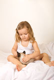 Little girl sitting in bed with her kitten Stock Photos