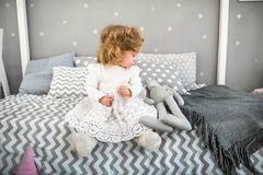 Little girl is sitting on the bed with her toy Stock Image