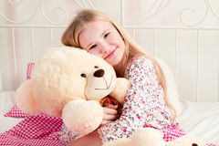 Little girl sitting on bed and hugging teddy bear. Cute little girl sitting on the bed and hugs a big teddy bear Royalty Free Stock Photography
