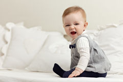Little girl sitting on bed and laughing Stock Images