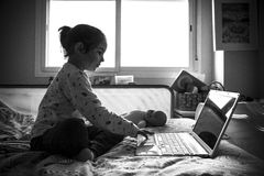 Little girl sitting in bed and playing games with laptop pc Royalty Free Stock Images