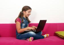 Little girl sitting on bed and playing laptop at home Stock Photography