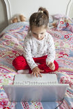 Little girl sitting in bed and playing online games Royalty Free Stock Photos
