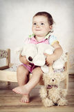 Little girl sitting on the bed with plush toys Stock Photography