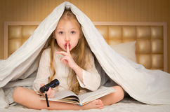 Little girl sitting on the bed and reading a book Royalty Free Stock Images