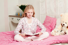 Little girl sitting on bed reading a book Stock Image