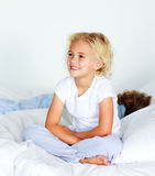 Little girl sitting on bed before sleeping Stock Image