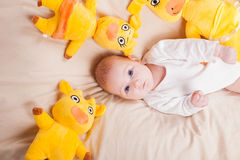 Little girl is sitting on a bed with soft toys stock photos