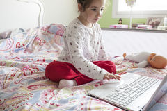 Little girl sitting in bed and surfing on Internet in his bedroo Royalty Free Stock Photography