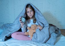 Little girl sitting on bed with teddy bear and alarm clock sleepless at night feeling restless. Cute sleepless little girl sitting on bed looking sad and tired royalty free stock photo