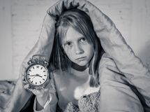 Little girl sitting on bed with teddy bear and alarm clock sleepless at night suffering insomnia royalty free stock photography