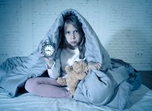 Little girl sitting on bed with teddy bear and alarm clock sleepless at night suffering insomnia. Cute sleepless little girl sitting on bed looking sad and tired royalty free stock image