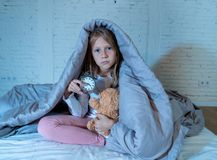 Little girl sitting on bed with teddy bear and alarm clock sleepless at night suffering insomnia. Cute sleepless little girl sitting on bed looking sad and tired royalty free stock photography