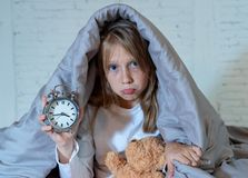 Little girl sitting on bed with teddy bear and alarm clock sleepless at night suffering insomnia. Cute sleepless little girl sitting on bed looking sad and tired royalty free stock photo