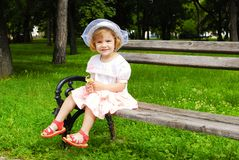 Little girl sitting on the bench Royalty Free Stock Photography