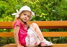 Little girl sitting on the bench stock photography