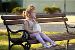 Little girl sitting on the bench Stock Image