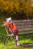 Little girl sitting on a bench in autumn Royalty Free Stock Image
