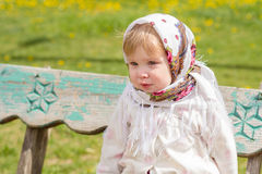 Little girl sitting on the bench. Little girl crying while sitting on the bench Stock Image