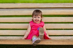 Little girl sitting on bench Royalty Free Stock Photos