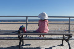 Little girl sitting on the bench looking out at the ocean Stock Photos
