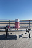 Little girl sitting on the bench looking out at the ocean Stock Photo