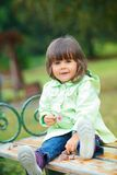 Little girl sitting on a bench in the park Stock Photography