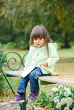 Little girl sitting on a bench in the park Royalty Free Stock Photography