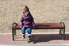 Little girl sitting of a bench Stock Photo