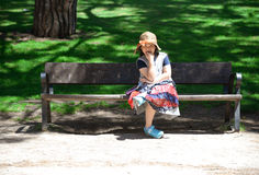 Little girl sitting on the bench in park. stock photography