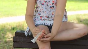 Little girl is sitting on the bench and cleaning her feet with wet tissue. Little girl is sitting on the bench in the park and cleaning her feet with wet tissue stock footage