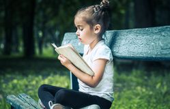 Little girl is sitting on a bench and is reading a book royalty free stock photo