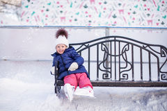 Little girl sitting on a bench in the skating rink Royalty Free Stock Photography