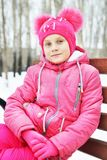 Little girl sitting on the bench in winter park Royalty Free Stock Photo