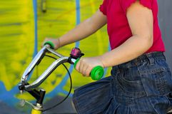 Little girl is sitting on a bicycle. Little girl in a red t-shirt and a denim skirt sits behind the wheel of a bicycle Stock Image