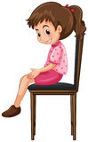 Little girl sitting on big chair Stock Images