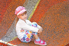 Little girl sitting on the big mosaic panel Stock Images