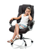Little girl sitting in big office armchair Stock Images
