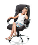 Little girl sitting in big office armchair Stock Photography