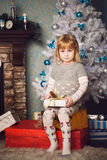 Little girl sitting on big present near the christmas tree Stock Photo
