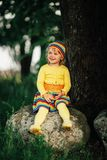 Little girl sitting on big stone Royalty Free Stock Photos