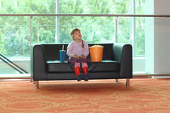 Little girl sitting on black sofa with popcorn Royalty Free Stock Image