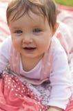 Little girl is sitting on blanket in garden Royalty Free Stock Image