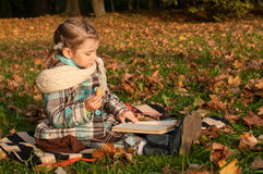 A a little girl sitting on a blanket and reading a book in a park, a lot of golden fallen leaves around Stock Image
