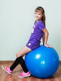 Little girl  is sitting on a blue fit ball at the gym Stock Image