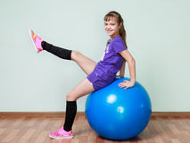 Little girl  is sitting on a blue fit ball, lifting the leg, smi Stock Images