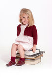 Little girl sitting on books Stock Images